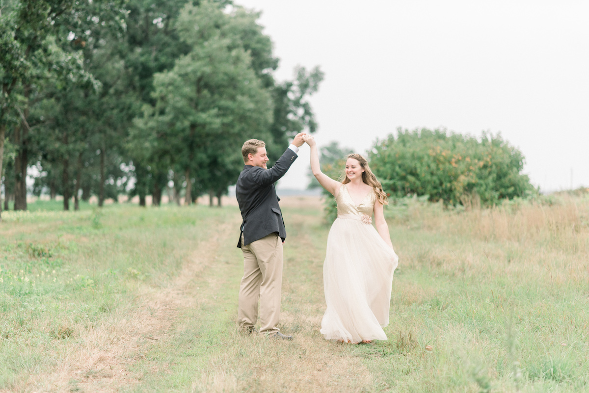 bride_smiling_while_groom_twirls_her_on_path_green_trees.jpg