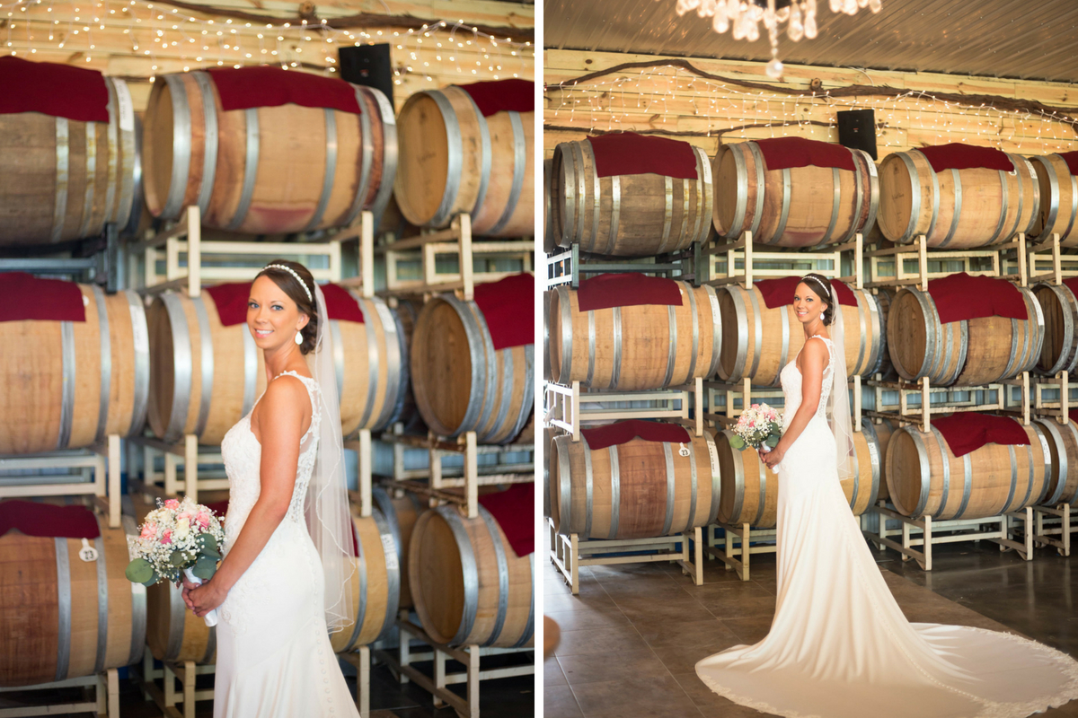 bride_standing_in_winery_barrels_behind_her_long_white_train.jpg