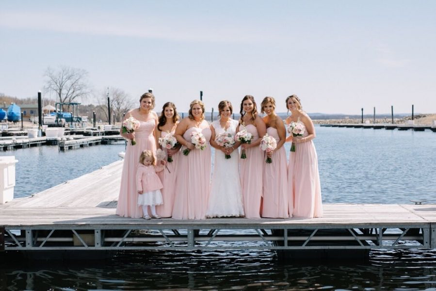 bride_standing_on_lake_dock_with_bridesmaid_and_flower_girl.jpg