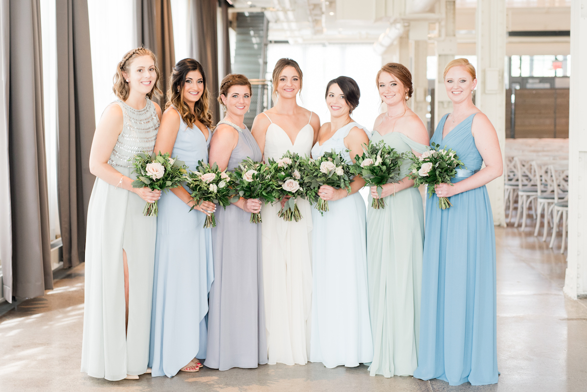 bride_standing_with_bridesmaids_in_cool_toned_mismatched_bridesmaid_dreses_holding_bouquets.jpg