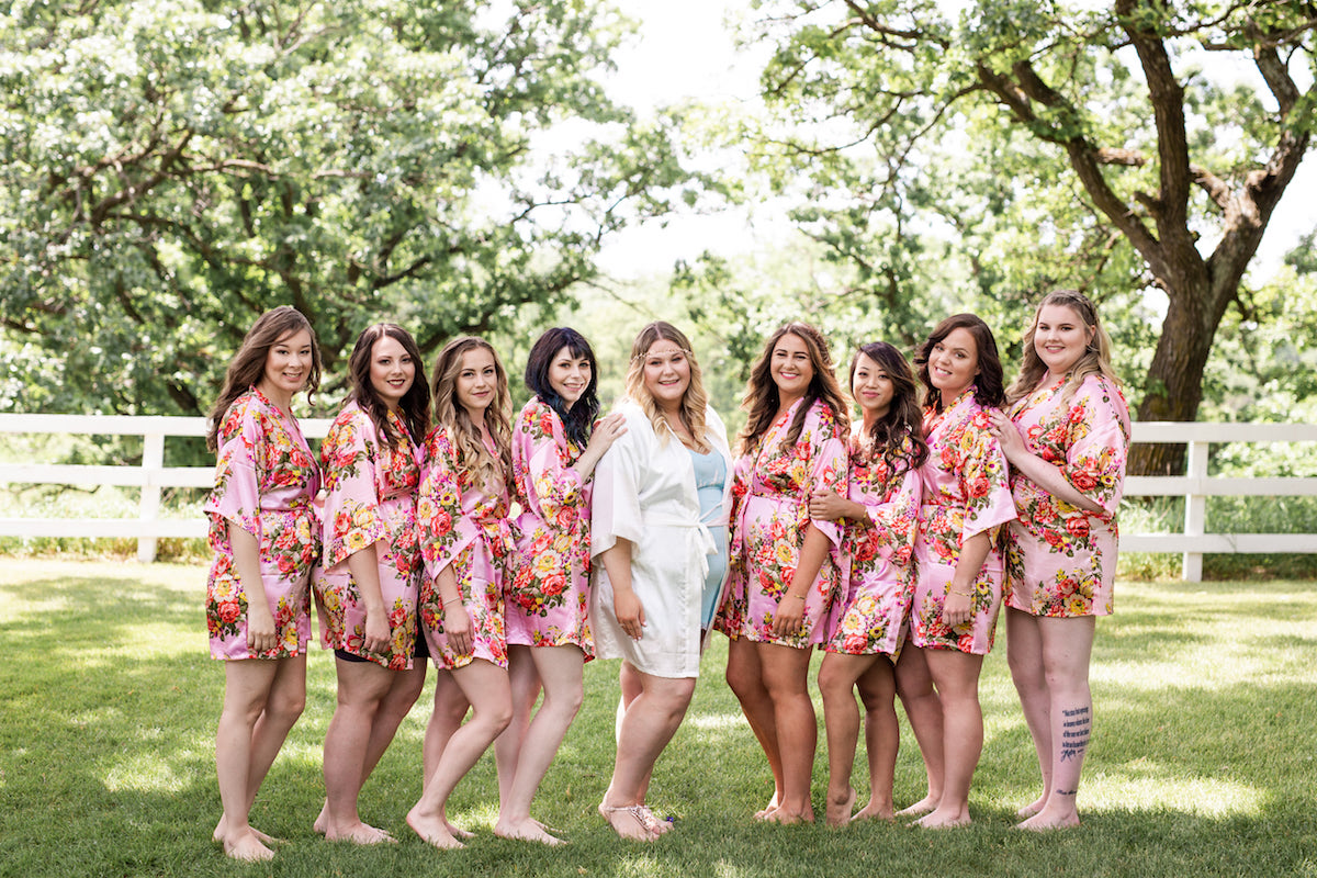 bride_standing_with_bridesmaids_in_pink_floral_robes_outdoors_in_grass.jpg