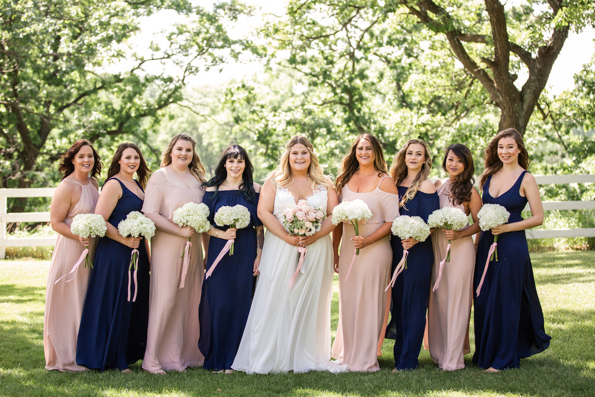 bride_standing_with_bridesmaids_outdoors_trees_in_background_pink_an_navy_bridesmaid_dresses.jpg