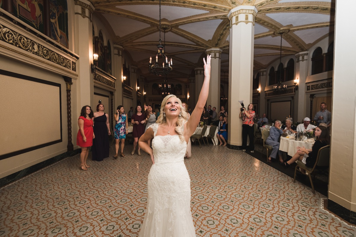 bride_tossing_bridal_bouquet_duluth_minnesota_ballroom_wedding.jpg