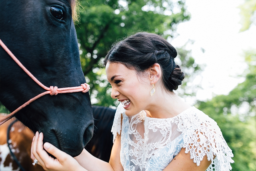 bride_updo_smiling_and_petting_black_horse.jpg