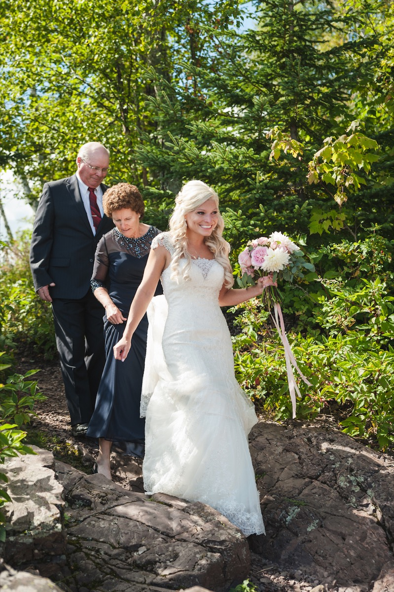 bride_walking_down_the_aisle_over_rocks_with_parents.jpg