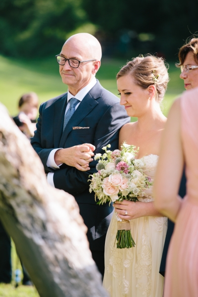 bride_walking_down_the_aisle_with_father_carrying_pink_white_bouquet.jpg