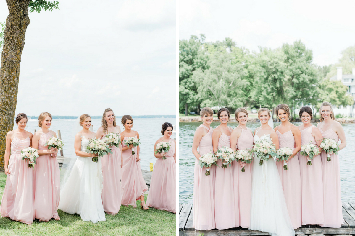 bride_walking_with_bridesmaids_in_baby_pink_dresses_lakeside_with_bouquets.jpg