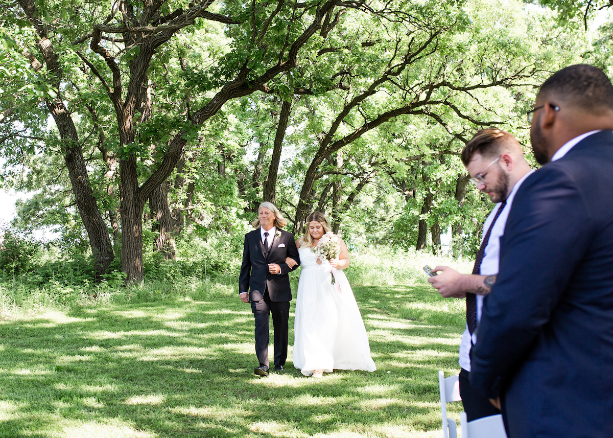 bride_walking_with_father_down_aisle_outdoor_wedding_venue_green_trees_background.jpg