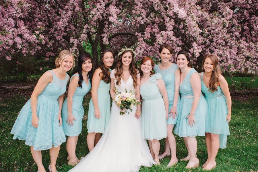 bride_with_bridesmaids_in_blue_standing_in_front_of_pink_cherry_blossoms.jpg