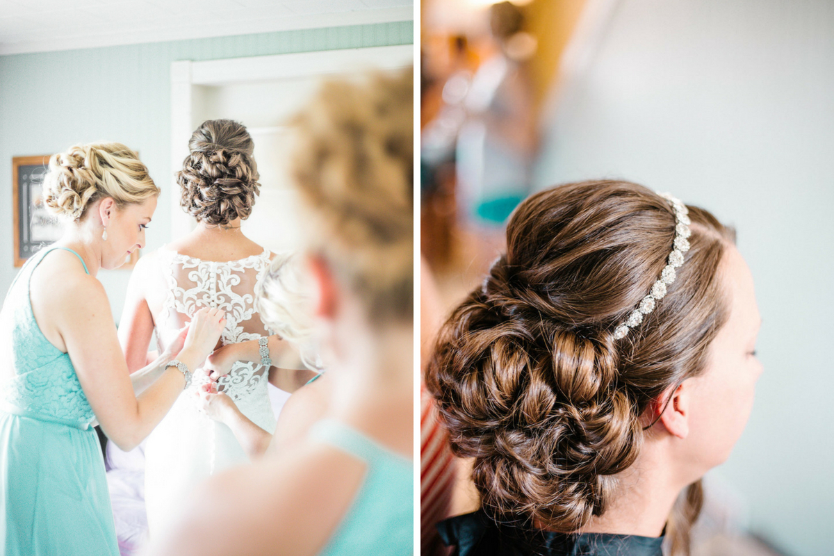bride_with_curly_bun_and_bridesmaids_buttoning_up_back_of_wedding_dress.jpg