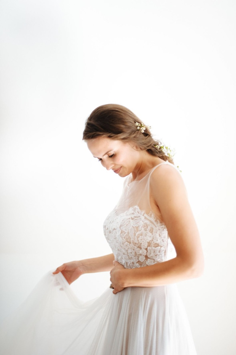 bride_with_greenery_flowers_in_braid_looking_down_holding_dress.jpg