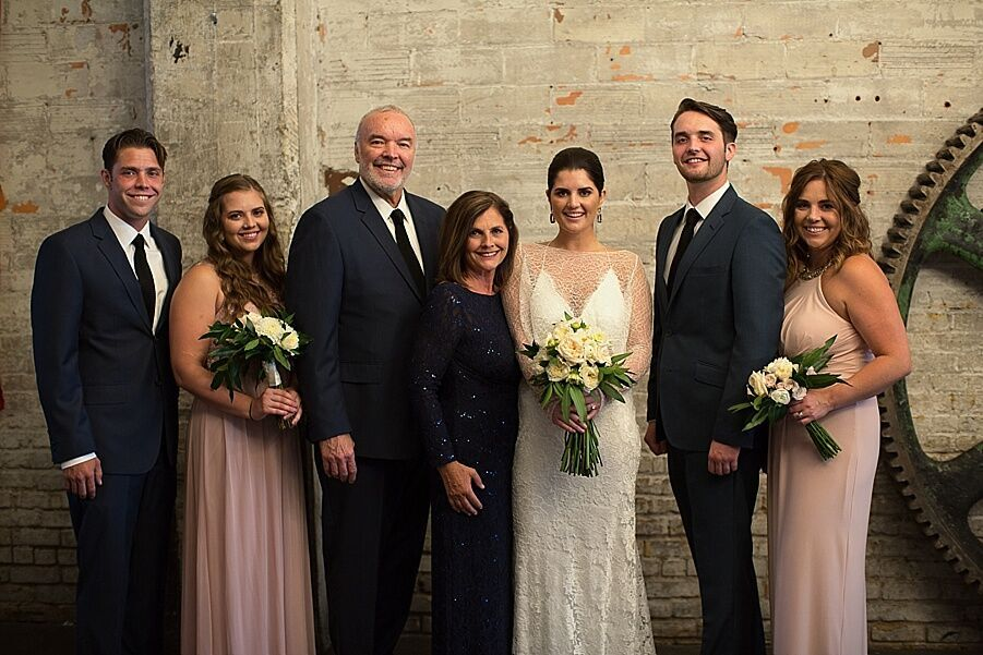 bride_with_her_family_blush_dresses_black_suits.jpeg