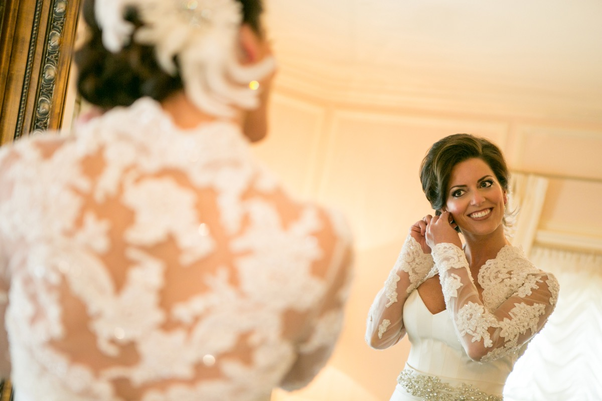 bride_with_updo_smiling_into_white_bridal_suite_gold_mirror_putting_on_white_earrings.jpg