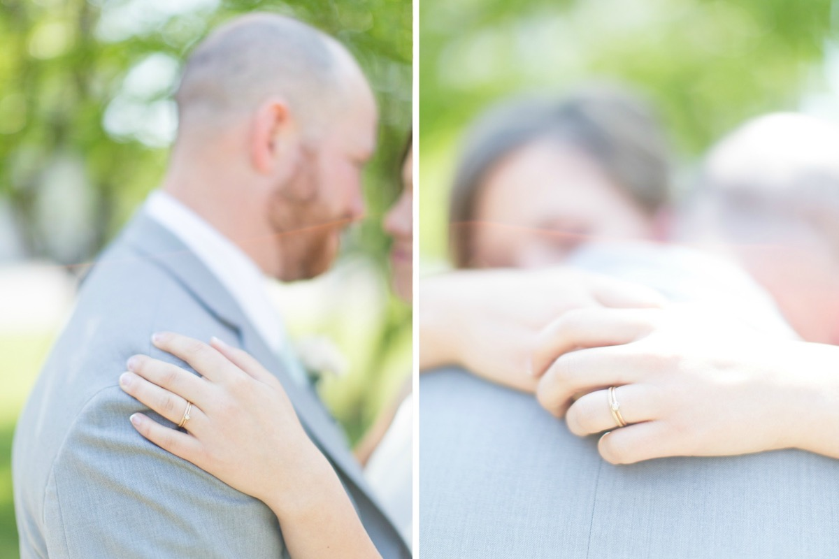 bride_wrapping_arms_around_grooms_neck_closeup_of_ring.jpg