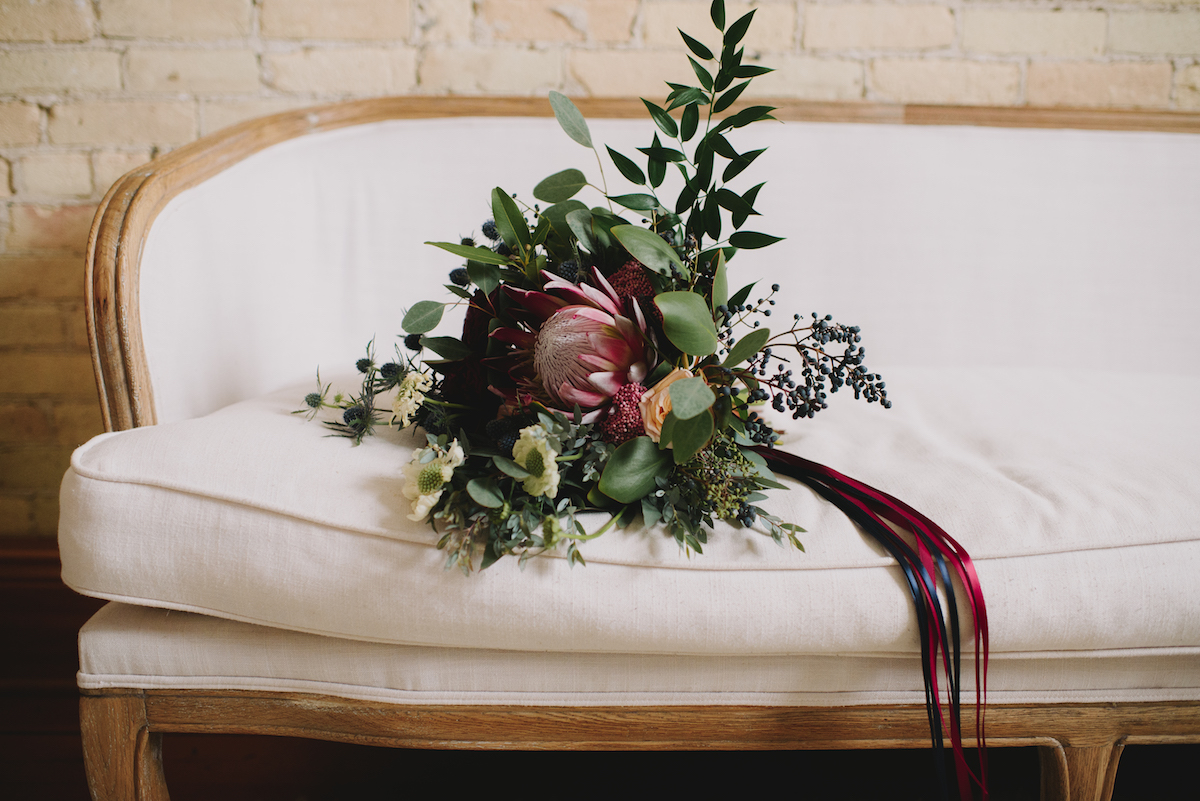 brides_winter_bouquet_laying_on_white_gold_couch.jpg