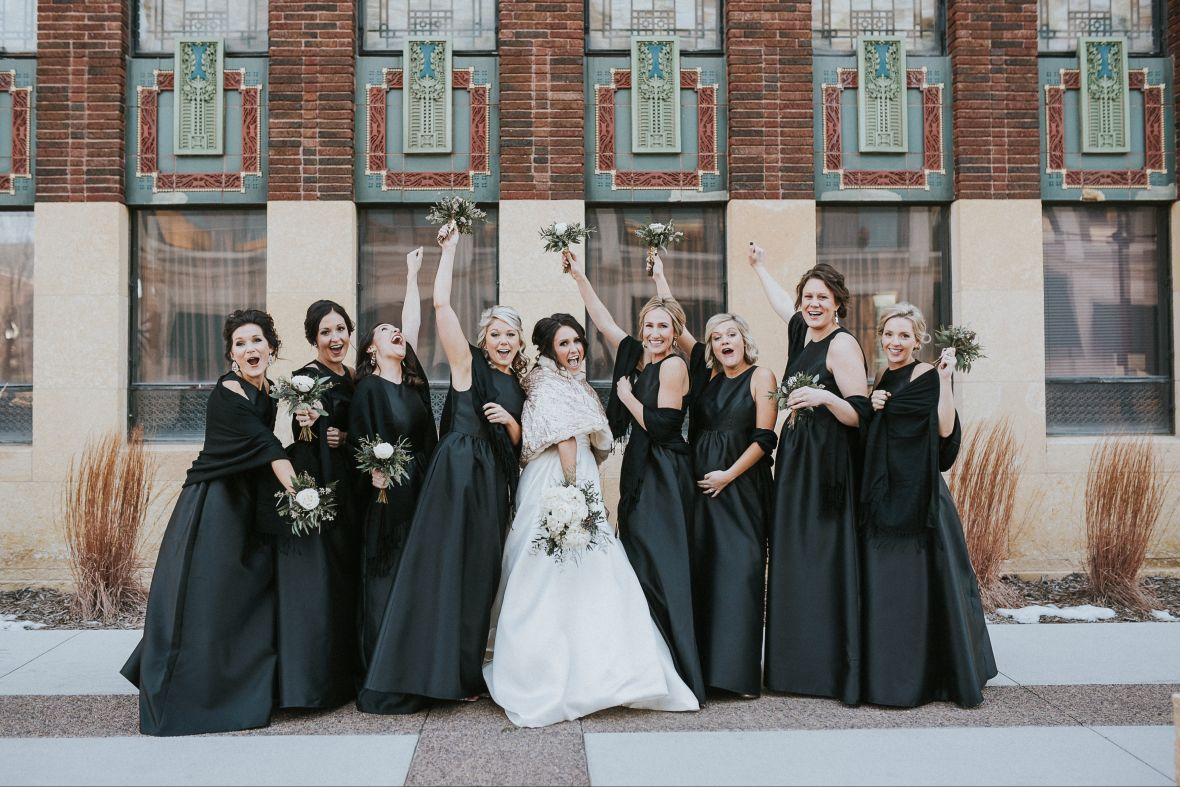 bridesmaids_black_dresses_holding_up_small_bouquets.jpg