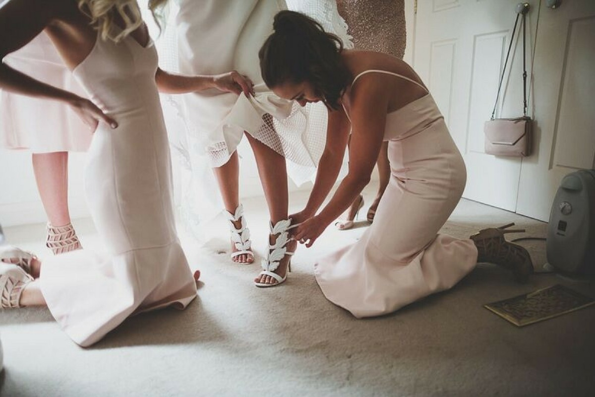bridesmaids_getting_brides_shoes_on.jpg