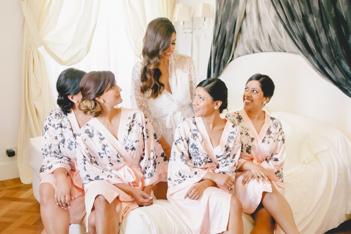 bridesmaids_sitting_on_bed_pink_floral_robes_.jpg