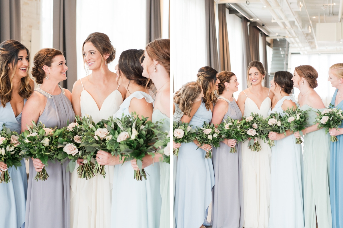 bridesmaids_smiling_at_bride_in_cool_toned_mismatched_dresses_holding_bouquets.jpg