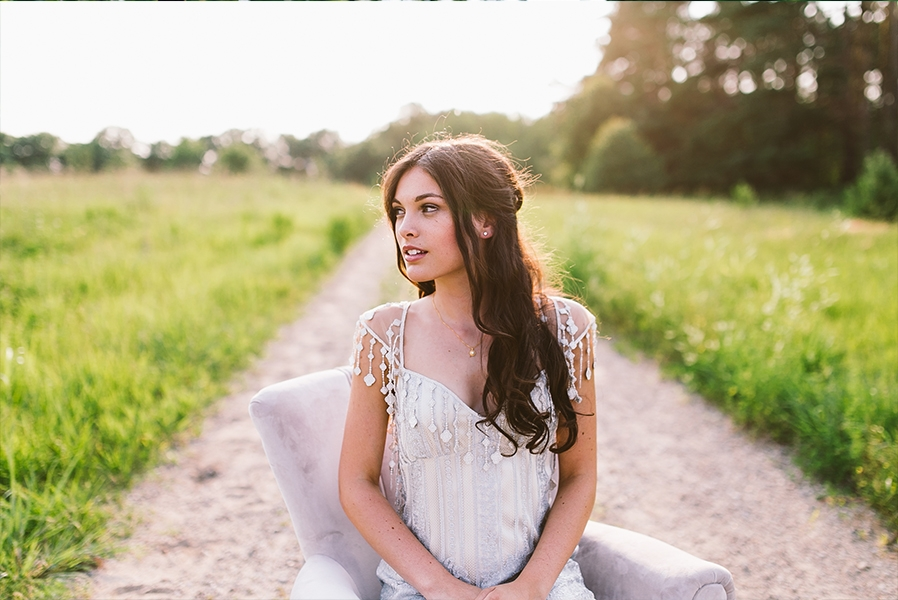 brunette_bride_looking_away_sitting_on_purple_chair_in_field.jpg