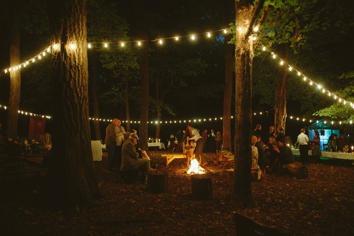 camp_wedding_in_woods_string_lights_in_trees_fire_wedding_reception.jpg