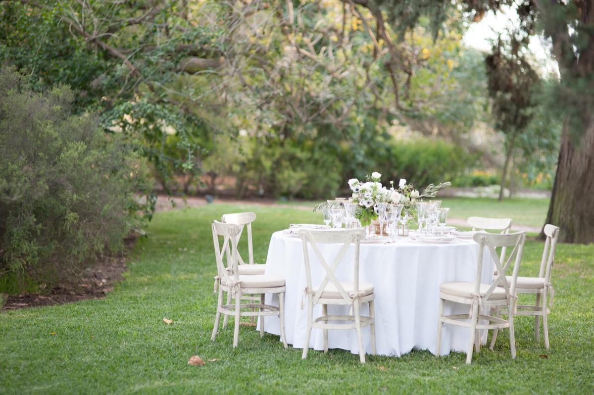 classy_white_wooden_chairs_table_outdoor_grass_wedding_reception.jpg