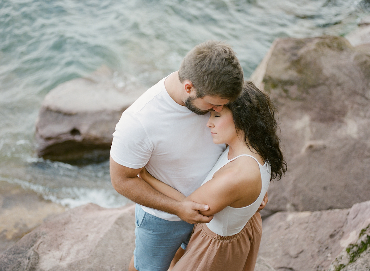 close_up_above_view_of_couple_embracing_intimately_on_cliffs_by_water.jpg