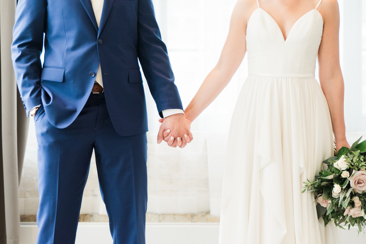close_up_bride_and_groom_holding_hands_navy_suit_simple_white_wedding_gown.jpg