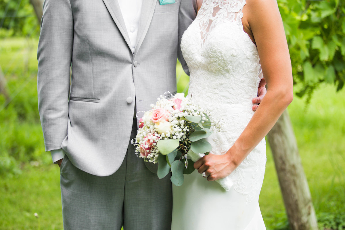 close_up_bride_and_groom_wedding_atire_lace_dress_grey_suit_floral_bouquet.jpg