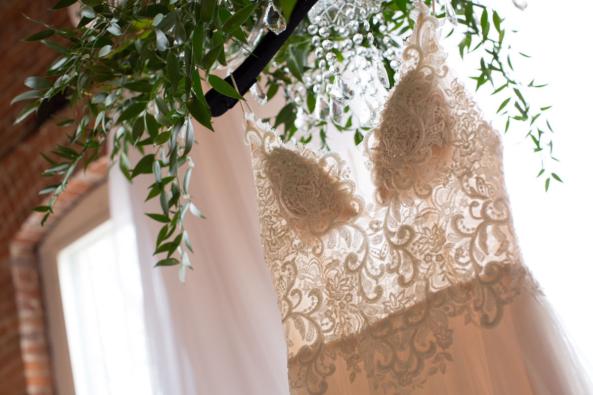 close_up_details_lace_wedding_gown_hanging_from_greenery_bouquet_brick_walls.jpg