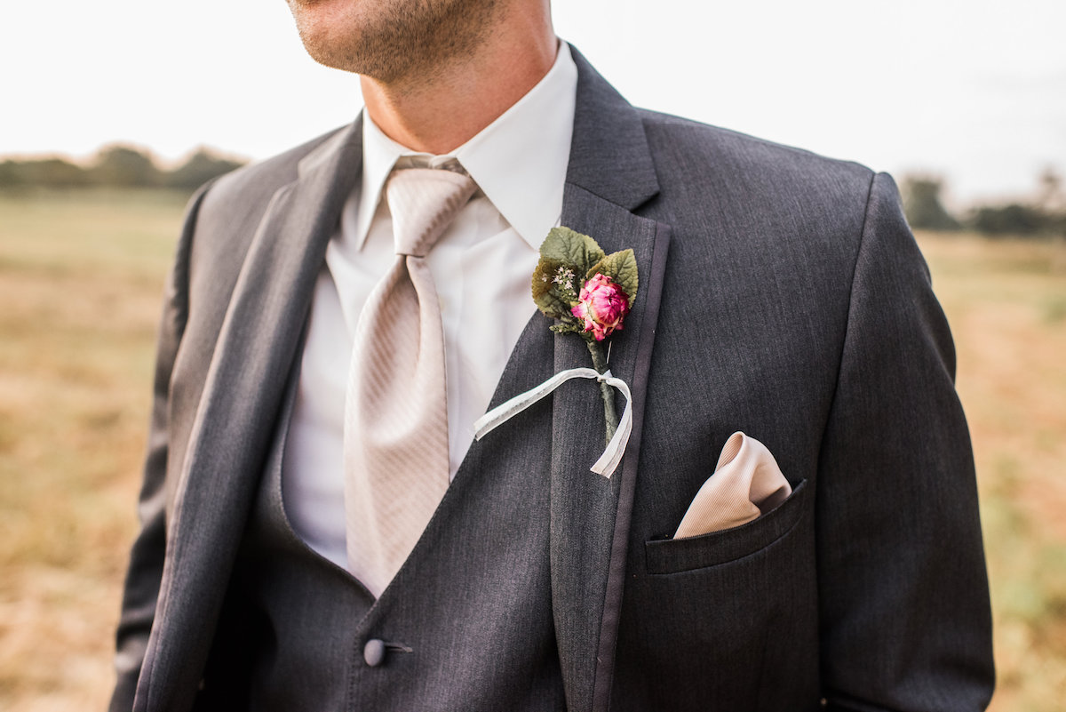 close_up_details_of_groom_in_golden_field_gray_suit.jpg