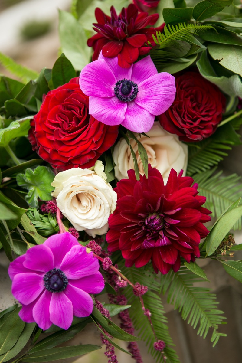 close_up_of_bridal_bouquet_bright_pink_red_flowers_with_greenery.jpg