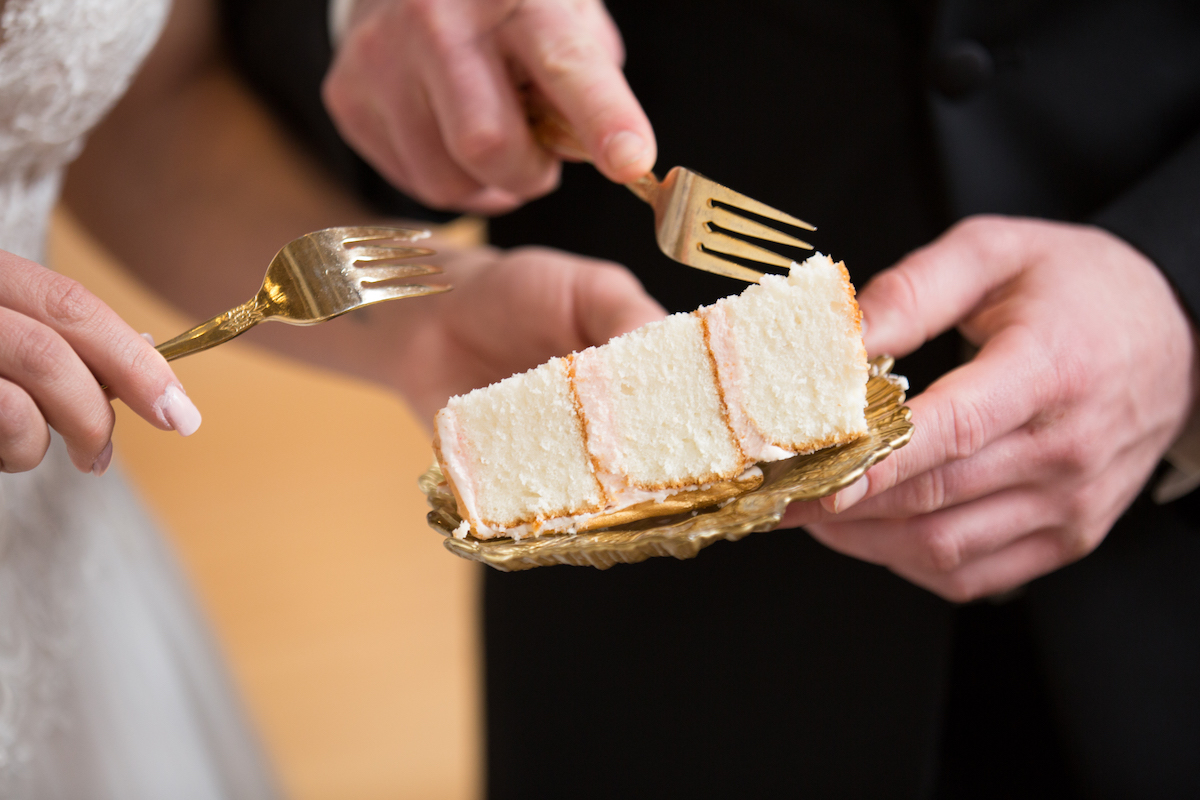 close_up_of_bride_and_groom_cutting_piece_of_cake_gold_forks_and_plate.jpg