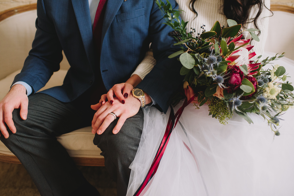 close_up_of_bride_and_groom_holding_hands_watch_and_jewelry.jpg