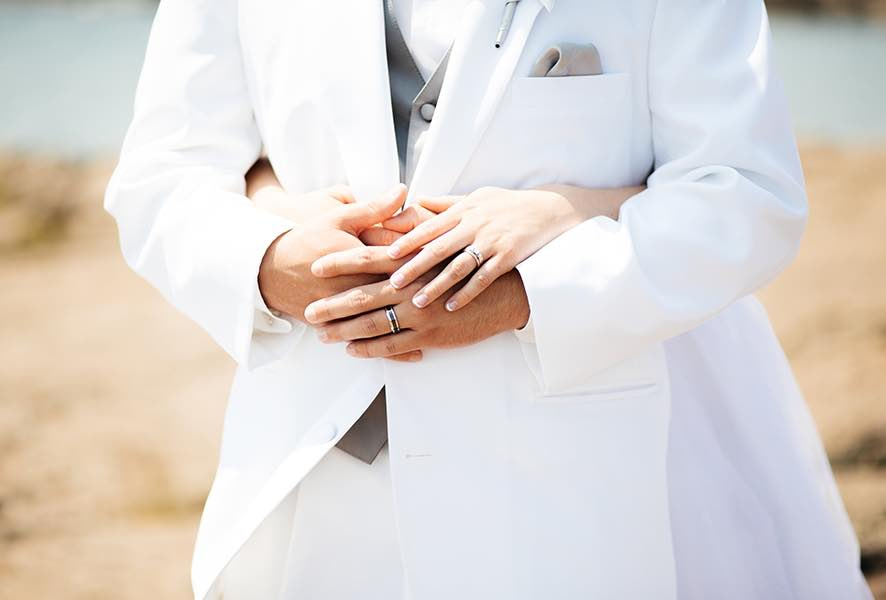 close_up_of_hands_bride_wrapping_arms_around_groom.jpg