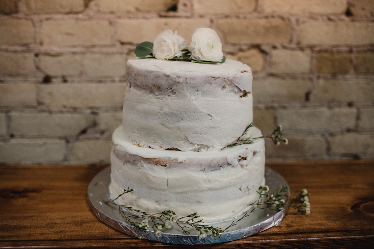 close_up_of_simplistic_white_wedding_cake_with_flowers.jpg