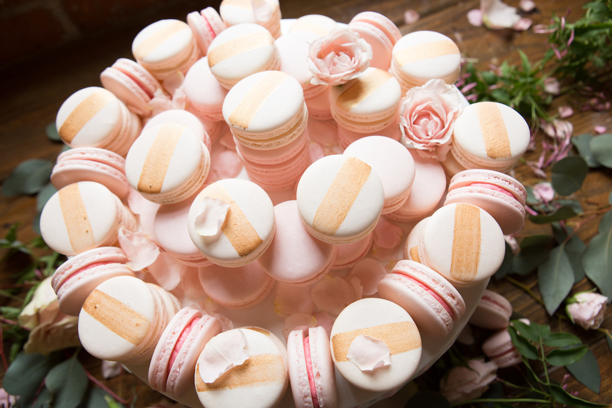 close_up_plate_full_of_gold_and_pink_wedding_macaroons.jpg