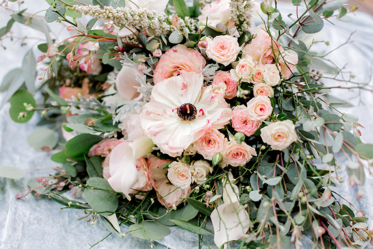 close_up_shot_light_pink_roses_floral_bouquet_laying_on_white_cloth.jpg