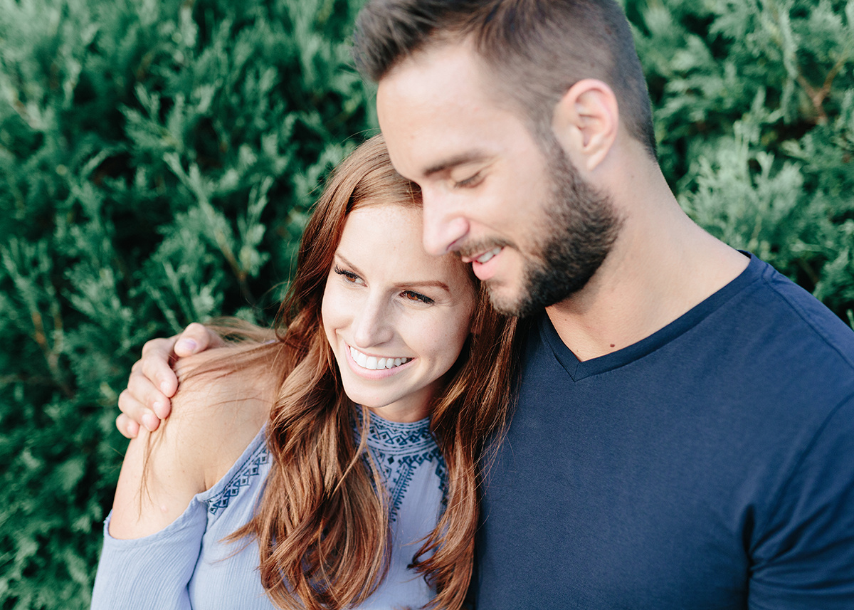 closeup_engaged_couple_smiling_leaning_against_shoulder.jpg