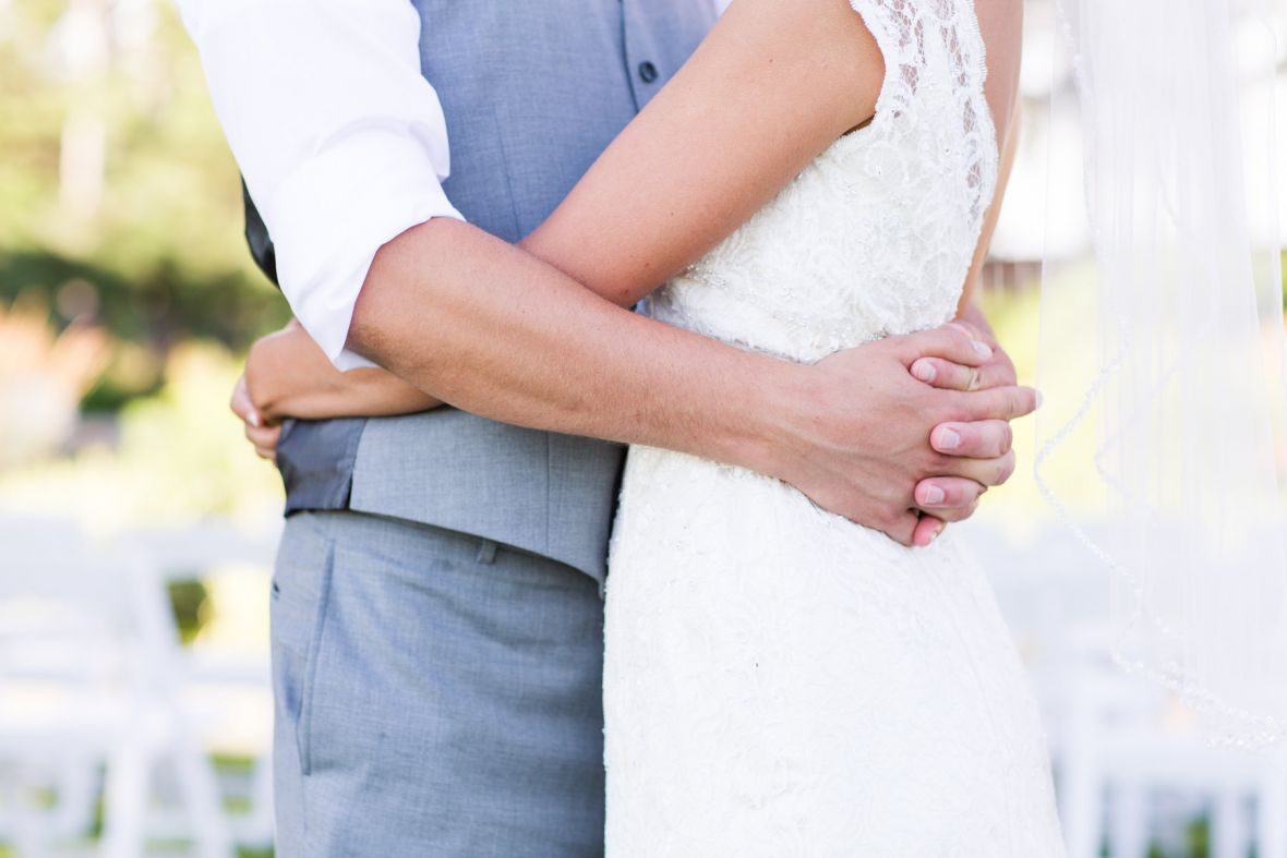 closeup_of_arms_wrapped_around_bride_and_groom.jpg