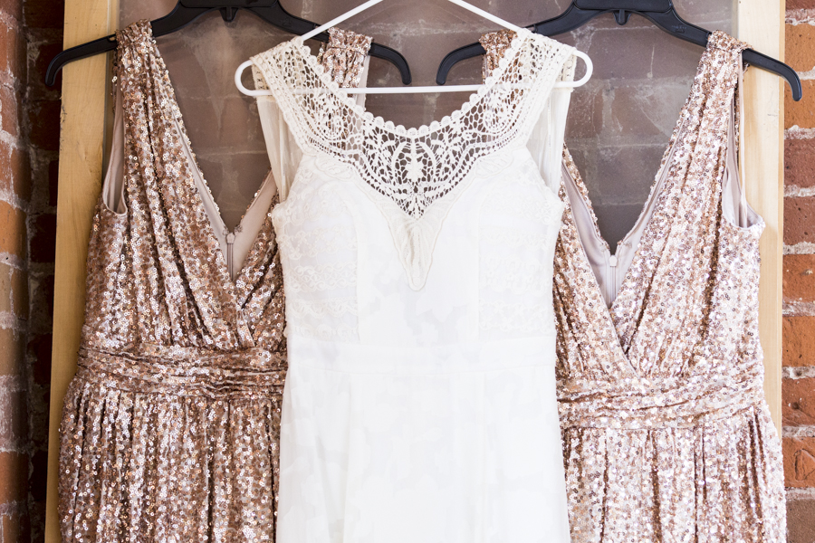closeup_of_bridal_gown_with_2_gold_sequin_bridesmaid_dresses.JPG
