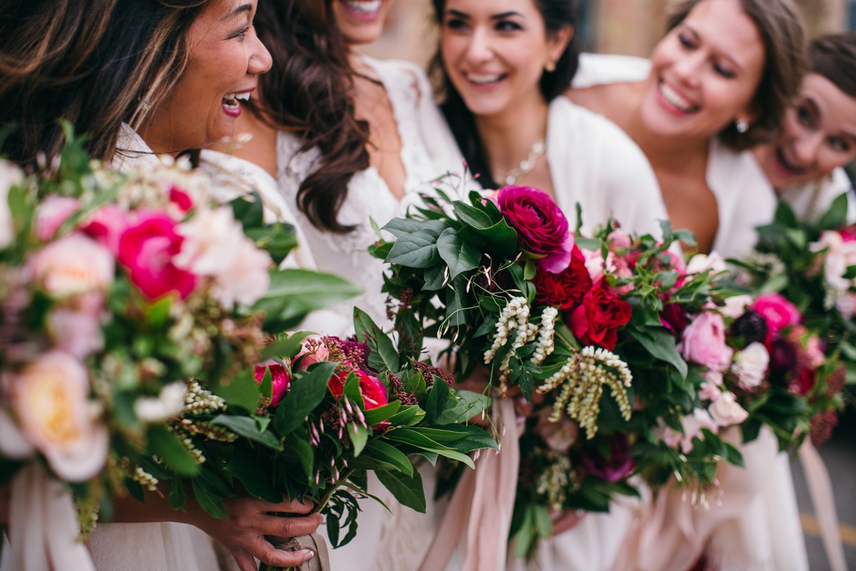 closeup_of_bridal_party_holding_red_bouquets.jpg
