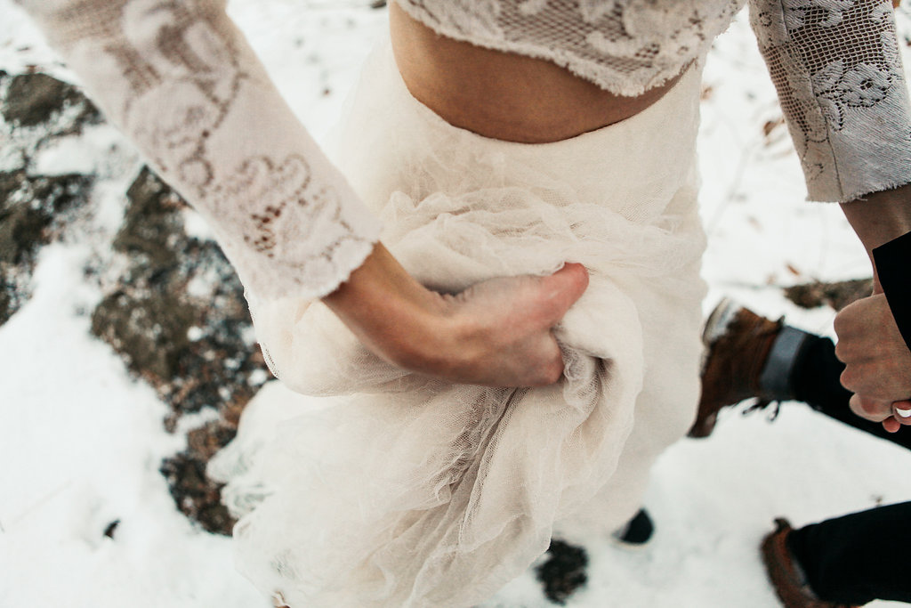 closeup_of_bride_holding_up_dress_in_the_snow.jpg