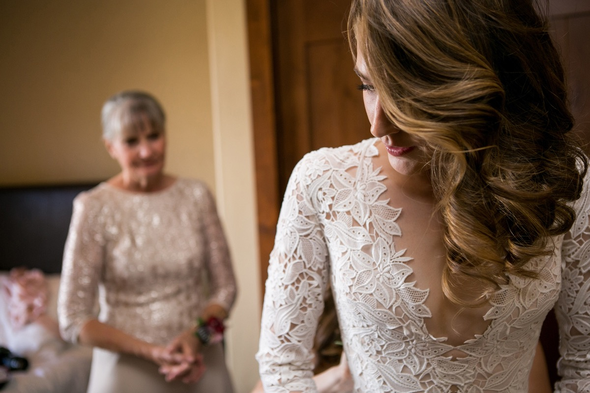 closeup_of_bride_in_lace_gown_mother_standing_behind.jpg