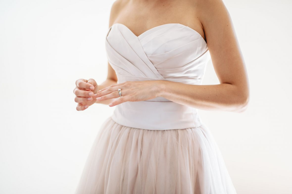 closeup_of_bride_touching_blush_nails_matching_dress.jpg