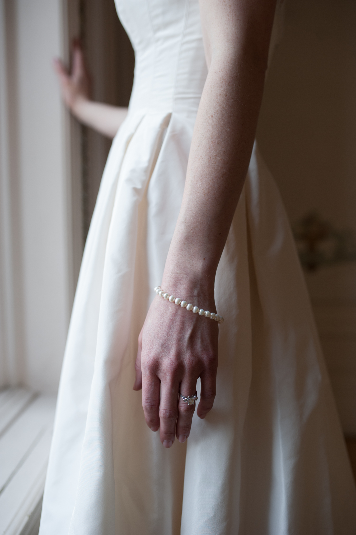 closeup_of_brides_wedding_ring_and_pearl_bracelet.jpeg