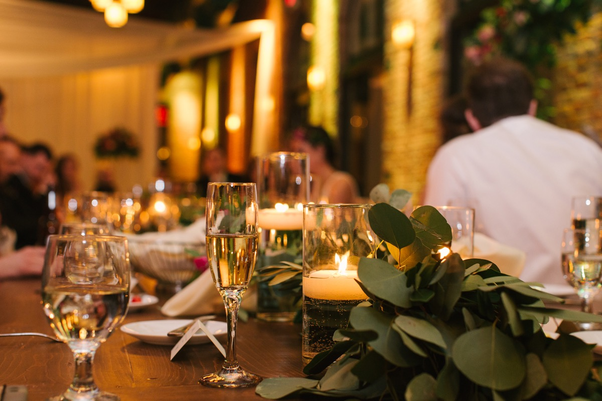 closeup_of_champage_glasses_candles_greenery_wedding_reception.jpg