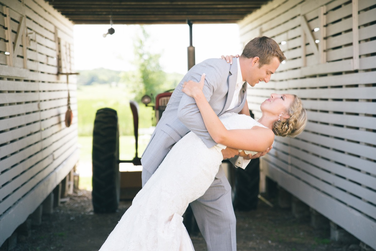 closeup_of_groom_dipping_bride_right_by_red_tractor.jpg