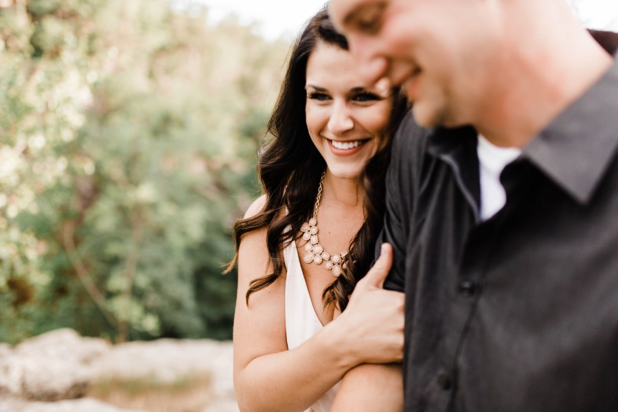 closeup_of_woman_linking_mans_arm_engagement_photos_forest.jpg