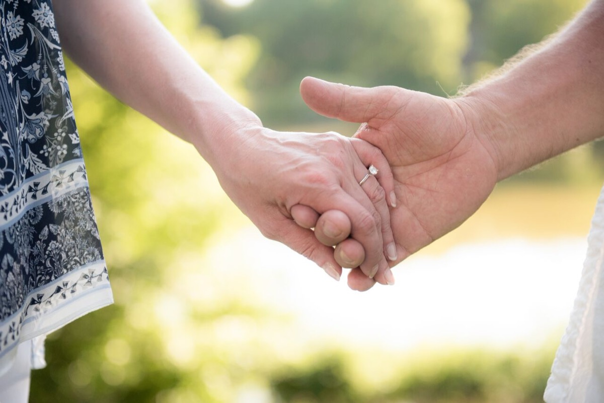 closeup_older_couple_holding_hands_wedding_ring.jpg